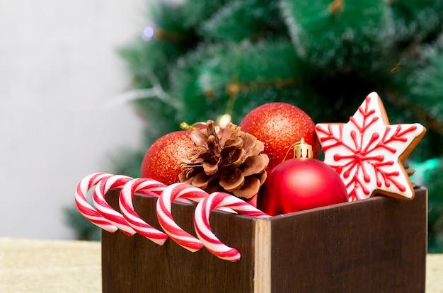 Kerstcadeausamenstelling met vuren kegel en feestelijke decoratie, peperkoek en suikerriet snoepjes in een donkerbruine doos met groene vachtboomtakken