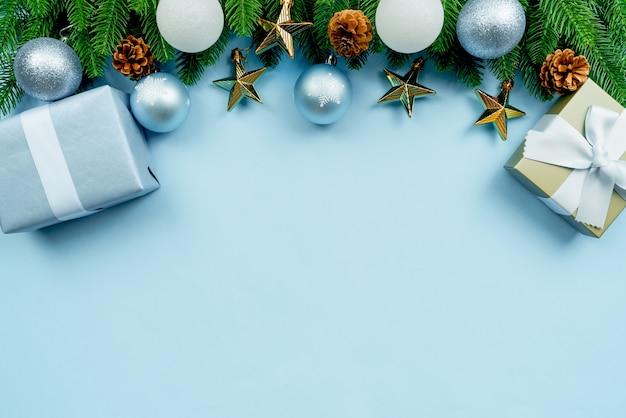 Kerstcadeautje en pijnboom met kerstmisdecoratie op blauwe achtergrond