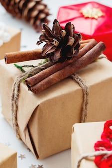 Kerstcadeautjes en decoraties. handgemaakt geschenk verpakt in ambachtelijke papieren dennenappel en kaneel.