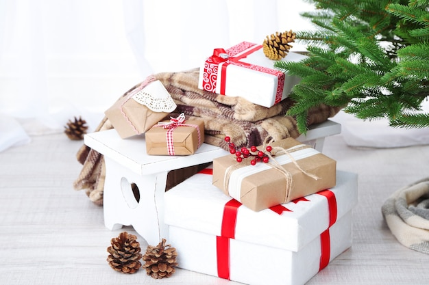 Kerstcadeautjes in de buurt van kerstboom op houten achtergrond