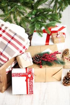 Kerstcadeautjes in de buurt van kerstboom op lichte achtergrond