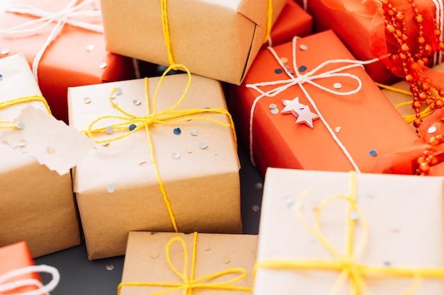 Kerstcadeautjes in geschenkdozen verpakt in ambachtelijke en rood papier gebonden met geel en wit touw. selectie handgemaakte pakketten.