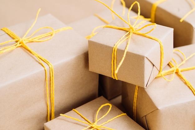 Kerstcadeautjes in geschenkverpakkingen verpakt in knutselpapier en vastgebonden met een geel touw. assortiment handgemaakte pakketten.