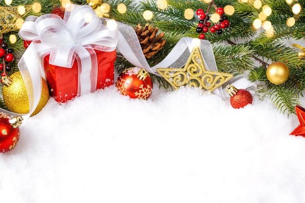 Kerstcadeautjes in rode dozen en kerstversieringen bij sneeuw