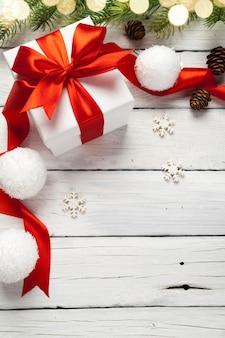 Kerstcadeautjes in rode dozen op witte houten tafel