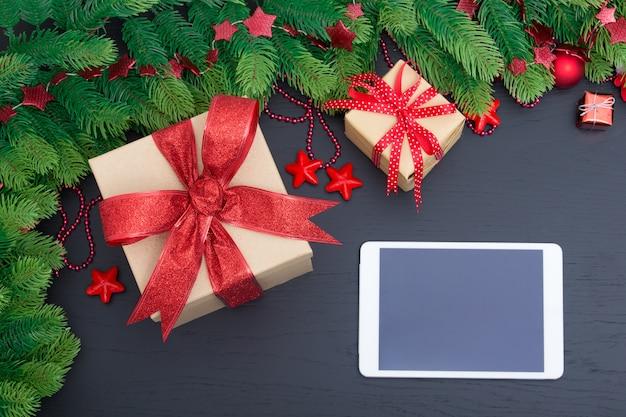 Kerstcadeautjes in rode dozen op zwarte houten tafel en tablet