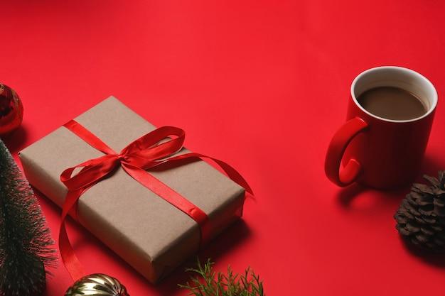 Kerstcadeautjes met rood lint, dennenappel, notebook en kopje koffie op rode achtergrond.