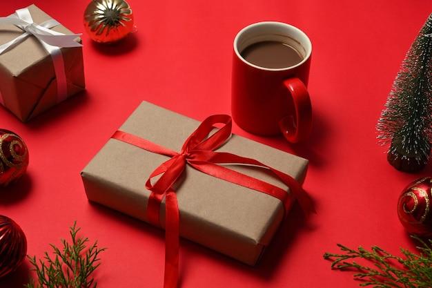 Kerstcadeautjes met rood lint en koffiekopje op rode achtergrond.