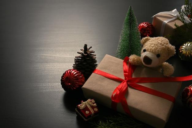 Kerstcadeautjes met rood lint, teddybeer, dennenappel op zwarte tafel.