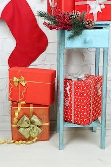 Kerstcadeautjes op blauwe boekenkast op bakstenen muur