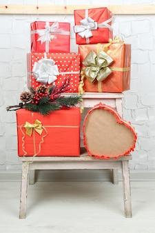 Kerstcadeautjes op ladder op bakstenen muur