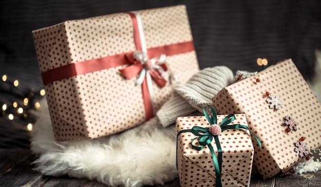 Kerstcadeautjes over lichten op donkere muur op gezellig tapijt. decoraties voor de feestdagen