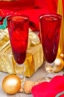 Kerstchampagne in rode glazen met gouden versieringen op houten tafel