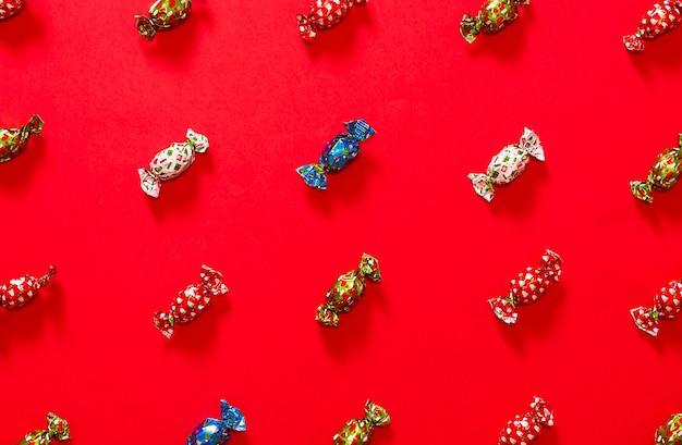 Kerstchocolaatjes die een patroon vormen op een rode achtergrond, afgewisseld met chocolaatjes met rood, groen, blauw en wit omhulsel
