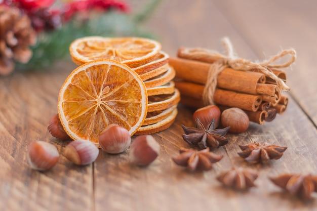 Kerstcompositie, arrangement van droge sinaasappelen kaneelstokjes en steranijs op houten achtergrond. rustieke, mediterrane, vakantiekruiden ingrediënten.