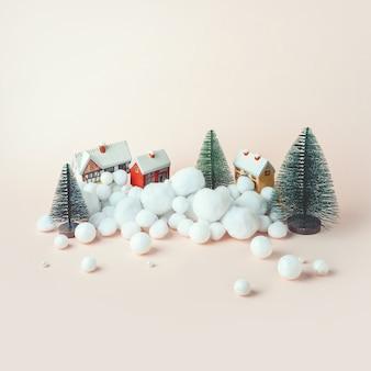 Kerstcompositie, decoratieve huizen in de winter tussen de bomen in de sneeuw
