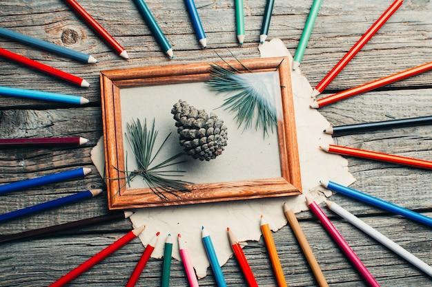 Kerstcompositie, fotolijst op houten tafel, boomtakken en kegels verspreid over verschillende kleuren