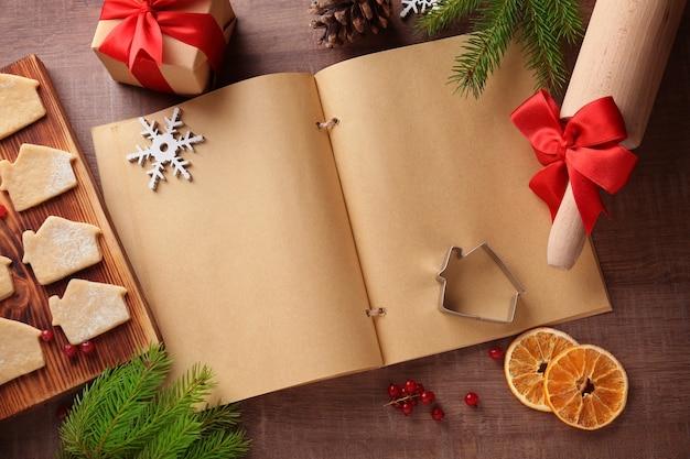 Kerstcompositie met blanco notitieboekje en rauwe kerstkoekjes op houten tafel