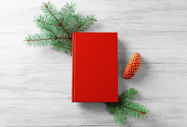 Kerstcompositie met boek en dennenboomtak