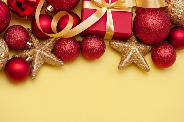 Kerstcompositie met decorsnuisterijen en geschenkdoos op gele achtergrond met kopieerruimte