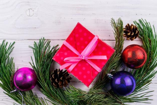 Kerstcompositie met dennentakken, geschenkdoos en kerstversiering op witte houten tafel. bovenaanzicht, kopieer ruimte
