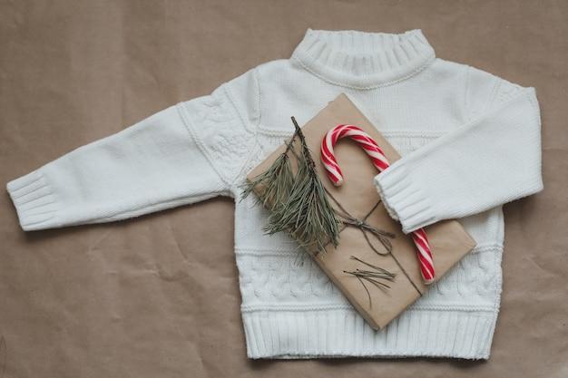 Kerstcompositie met een gebreide trui en een cadeau kerst winter nieuwjaar concept plat lag t...