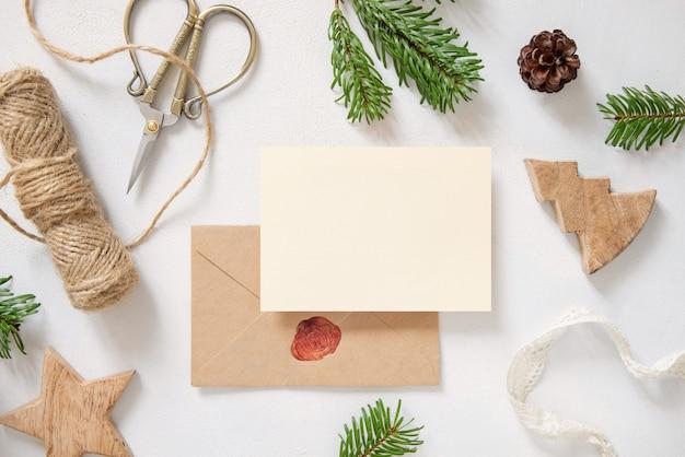 Kerstcompositie met een kaart over een verzegelde envelop plat gelegd