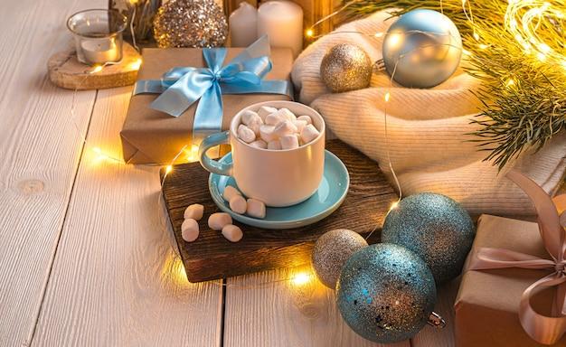 Kerstcompositie met een kopje koffie, kerstboomspeelgoed en een geschenk verlicht door een slinger. het concept van kerstmis en nieuwjaar. zijaanzicht, kopieer ruimte.