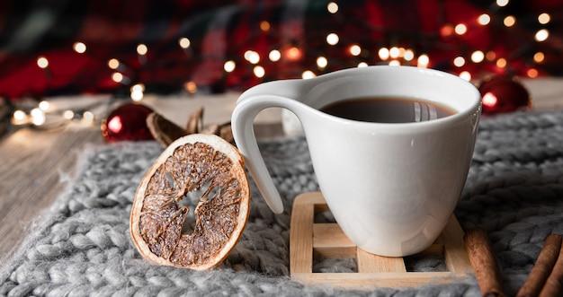 Kerstcompositie met een kopje thee, gedroogde sinaasappelen, kruiden op een onscherpe achtergrond.