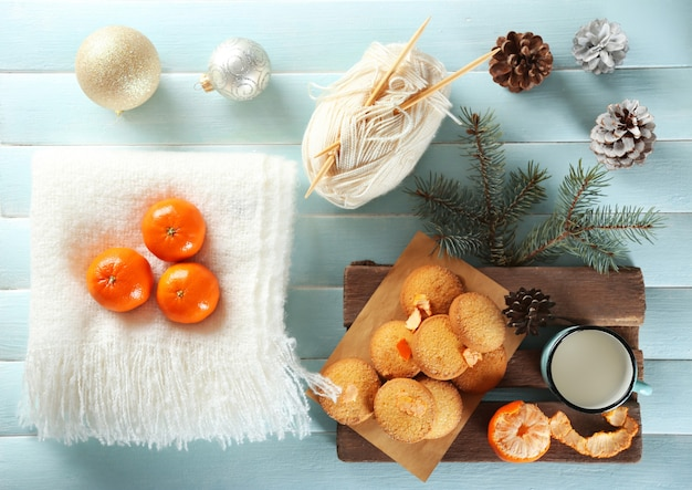 Kerstcompositie met een sjaal, koekjes en versieringen op een blauwe tafel
