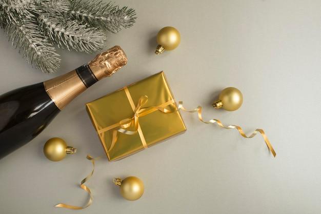 Kerstcompositie met fles champagne en gouden geschenkdoos op de grijze achtergrond
