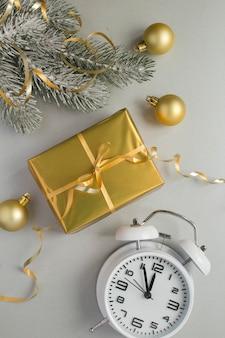 Kerstcompositie met geschenkdoos en witte wekker op de grijze achtergrond. bovenaanzicht.