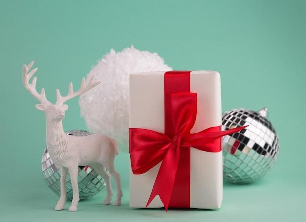 Kerstcompositie met geschenkdozen met rode strik, feestelijk decor, sneeuwballen en hertenbeeldje