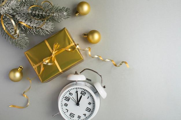 Kerstcompositie met gouden geschenkdoos en witte wekker op de grijze achtergrond. bovenaanzicht. ruimte kopiëren.