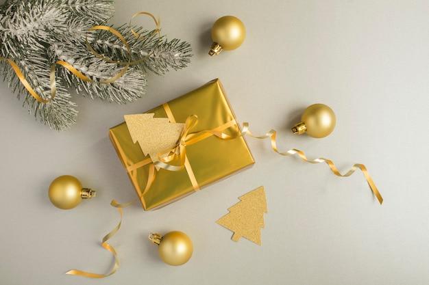 Kerstcompositie met gouden geschenkdoos op de grijze achtergrond. bovenaanzicht. ruimte kopiëren.