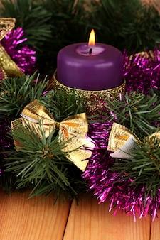 Kerstcompositie met kaarsen en decoraties in paarse en gouden kleuren op houten achtergrond