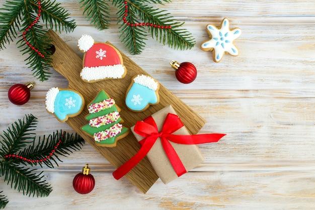 Kerstcompositie met peperkoek en geschenkdoos op de snijplank op de houten achtergrond. bovenaanzicht. ruimte kopiëren.