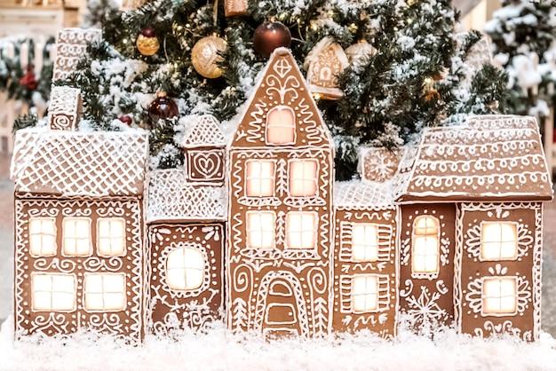 Kerstcompositie met peperkoekhuizen die op een rij staan op de achtergrond van de kerstboom