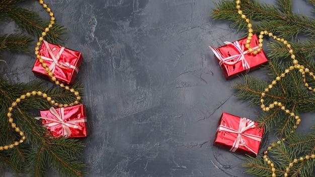 Kerstcompositie met rode geschenken en kerstboom op donkere achtergrond, wenskaart, wintervakantie