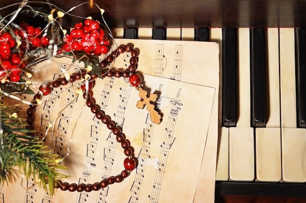 Kerstcompositie met rozenkrans en muziekblad op piano