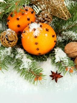 Kerstcompositie met sinaasappelen en dennenboom, geïsoleerd op wit