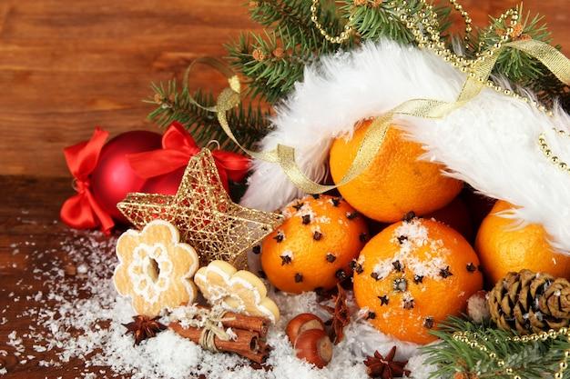 Kerstcompositie met sinaasappelen en dennenboom in kerstmanhoed