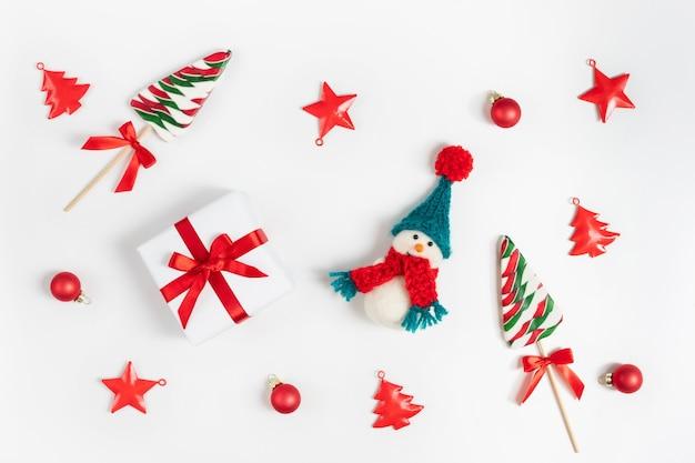 Kerstcompositie met sneeuwpop, lolly's en kerstversiering.