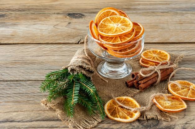 Kerstcompositie met vuren boomtakken, kaneelstokjes en slinger gemaakt van gedroogde plakjes sinaasappel op houten achtergrond. rustieke stijl.