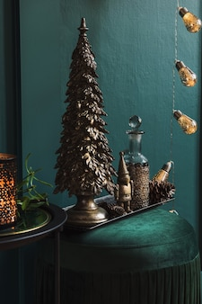Kerstcompositie op de groene fluwelen poef in de woonkamer. mooie decoratie. kerstbomen, kaarsen, sterren, lichtjes en elegante accessoires.