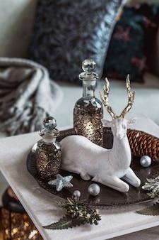 Kerstcompositie op de marmeren tafel in het interieur van de woonkamer met prachtige decoratie. kerstboom, herten, kaarsen, sterren, licht en elegante accessoires. vrolijk kerstfeest.