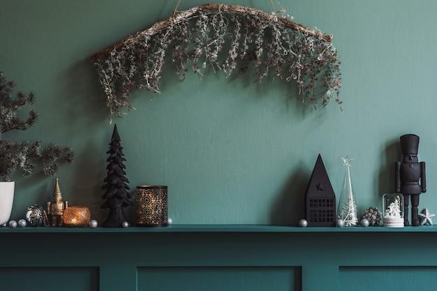 Kerstcompositie op de plank in het interieur van de woonkamer. mooie decoratie. kerstbomen, kaarsen, sterren, licht en elegante accessoires.