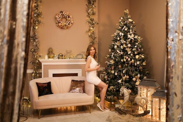 Kerstconcept, een meisje met een kapsel in een jurk poseert bij een boom in een chique ingericht interieur