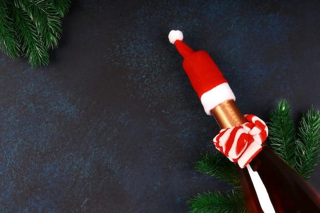 Kerstconcept. fles champagne in een rode kerstmuts met vuren takken op een donkerblauwe achtergrond. bovenaanzicht, vlakke stijl, plaats voor tekst