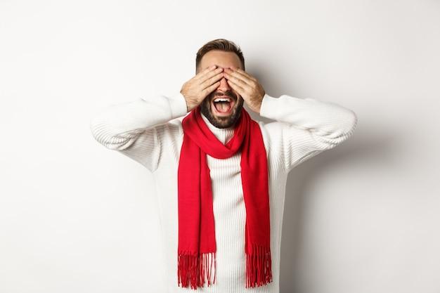 Kerstconcept. gelukkige man sluit zijn ogen en wacht op geschenken, glimlachend opgewonden, nieuwjaar vieren, wintervakanties, staande op een witte achtergrond
